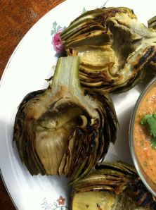 Photo of grilled artichoke halves with a sliver of Gazpacho showing.