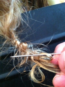 Photo of sewing needle used to untangle knotted hair.