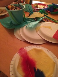 Tissue paper, paper plates, crayons, glue, hole punch, feathers, pompoms and pipe cleaners.