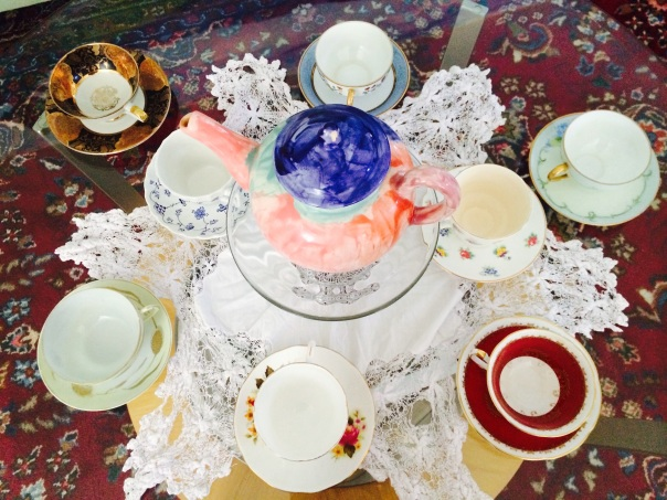 Vintage tea cups laid out on a glass table.