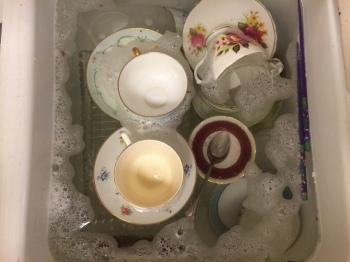 Vintage teacups in warm soapy water.